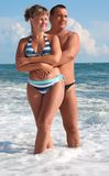 Couple stand in sea waves Stock Photography