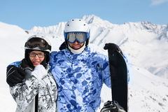 Couple stand with snowboard and skis Stock Photos