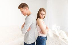 A couple stand with their backs against each other because of an argument. Indoors bedroom. royalty free stock image