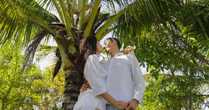 Couple Stand Under Palm Tree Kiss Embracing In Tropical Garden , Happy Man And Woman Outdoors. Slow Motion 60 stock footage