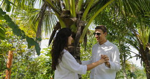 Couple Stand Under Palm Tree Kiss Talking In Tropical Garden , Happy Man And Woman Outdoors. Slow Motion 60 stock video
