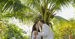 Couple Stand Under Palm Tree Kiss Talking In Tropical Garden , Happy Man And Woman Outdoors. Slow Motion 60 stock footage