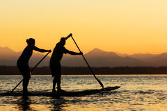 Couple on Stand Up Paddle Boards. With sun and mountains in background Stock Photo