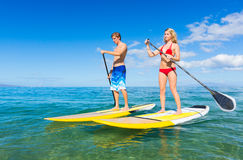 Couple Stand Up Paddle Surfing In Hawaii Royalty Free Stock Photo