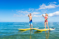Couple Stand Up Paddling in Hawaii Stock Images
