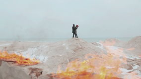 Couple standing against a background of fire, on the hill of sand. Winter sea. Young people hugging, kissing and warm each other`s hands on the beach in winter stock video footage