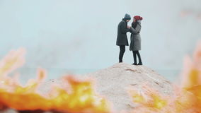 Couple standing against a background of fire, on the hill of sand. Winter sea. Young people hugging, kissing and warm each other`s hands on the beach in winter stock footage