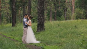 Couple standing arm in arm at wedding photo shoot in woods outdoors stock video footage