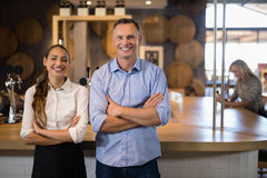 Couple standing with arms crossed near bar counter Stock Photo