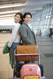 Couple standing back to back behind luggage trolley in airport, smiling, side view, portrait Royalty Free Stock Photo