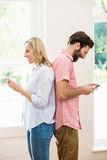 Couple standing back to back and text messing on mobile phone. At home Royalty Free Stock Images