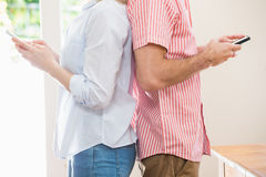 Couple standing back to back and text messing on mobile phone. Mid section of couple standing back to back and text messing on mobile phone at home Stock Images