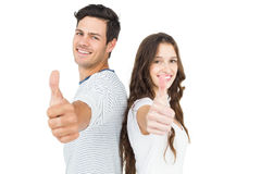 Couple standing back to back with thumbs up. On white background Royalty Free Stock Images