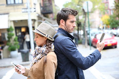 Couple standing back to back using smartphones Royalty Free Stock Images