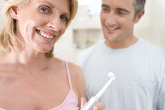 Couple standing in bathroom, woman holding up toothbrush, smiling, portrait Stock Photos