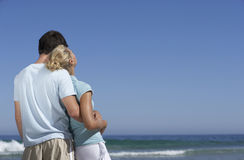 Couple standing on beach, looking at horizon over sea, man embracing woman, rear view Royalty Free Stock Photography