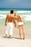 Couple standing on the beach looking at the ocean Royalty Free Stock Photo