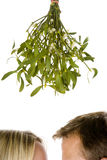 Couple Standing Beneath Mistletoe Stock Photos