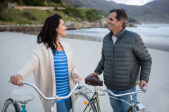 Couple standing with bicycle interacting with each other on beach Stock Photos