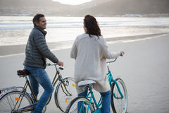 Couple standing on bicycle interacting with each other on beach Stock Images
