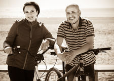 Couple standing with the bicycles. portrait of a happy mature couple standing with the bicycles Royalty Free Stock Images