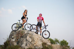 Couple standing with bicycles on the rock under evening sky Stock Photography