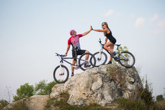 Couple standing with bicycles on the rock under evening sky Royalty Free Stock Image