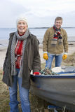 Couple standing by boat on beach Stock Images