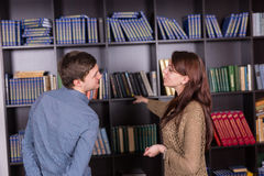 Couple Standing Beside Bookshelves at the Library Stock Photo