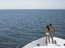 Couple Standing On Bow Of Yacht Looking At Seascape Stock Images