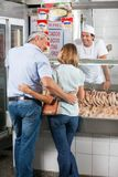 Couple Standing In Butcher's Shop Stock Images