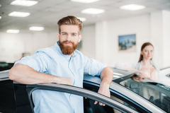 Couple standing at car in dealership salon, man looking at camera Stock Image