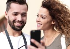 Happy young couple searching for location both on mobile phone. Couple standing in a city during there trip Stock Images
