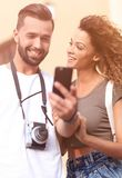 Happy young couple searching for location both on mobile phone. Couple standing in a city during there trip Royalty Free Stock Photo