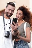 Happy young couple searching for location both on mobile phone. Couple standing in a city during there trip Stock Photos