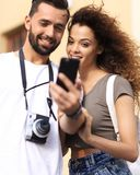 Happy young couple searching for location both on mobile phone. Couple standing in a city during there trip Royalty Free Stock Images