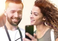Happy young couple searching for location both on mobile phone. Couple standing in a city during there trip Royalty Free Stock Photos
