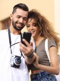 Happy young couple searching for location both on mobile phone. Couple standing in a city during there trip Stock Photography