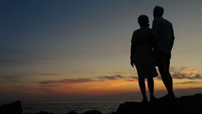 Couple standing on the cliff of a mountain holding hands and watching sunset stock video footage