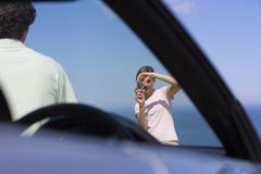 Couple standing on clifftop overlooking Atlantic Ocean, woman photographing man beside car Royalty Free Stock Photography