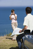 Couple standing on clifftop overlooking Atlantic Ocean, woman photographing man with map beside car Royalty Free Stock Photo