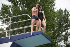 Couple standing on diving board at swimming pool Royalty Free Stock Images