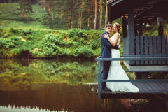 The couple standing on the dock. The couple are in an embrace by the river Stock Photography