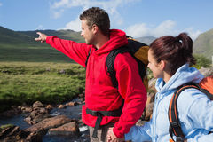 Couple standing at edge of river on a hike with man pointing Stock Photography