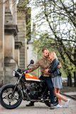 Couple standing and embracing near the motorcycle in the old city background Royalty Free Stock Photo