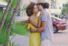 Couple standing and embracing on the street. Side view of adult ethnic men and women standing together and embracing on the street in sunny day stock photography