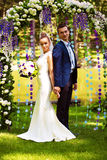 Couple standing in flower arch Royalty Free Stock Photography