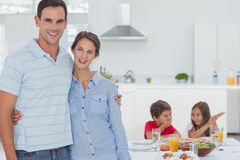 Couple standing in front of children at the table Stock Photos
