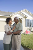 Couple Standing In Front Of House For Sale Stock Photos