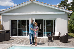 Couple standing in front of newly owned house Stock Photos